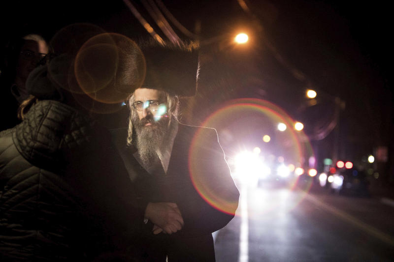 Orthodox Jewish people gather on a street in Monsey, N.Y., on early Sunday, Dec. 29, 2019, following a nearby stabbing late Saturday at a Hanukkah celebration. A knife-wielding man stormed into a rabbi's home and stabbed five people in the Orthodox Jewish community north of New York City. (AP Photo/Allyse Pulliam)