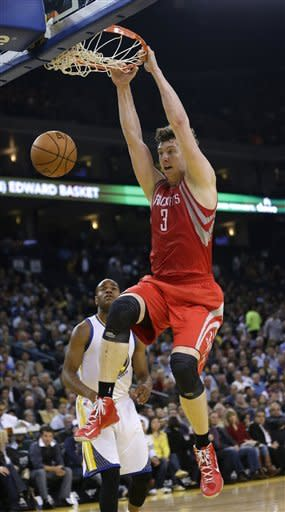 Houston Rockets' Omer Asik (3) dunks next to Golden State Warriors' Jarrett Jack during the first half of an NBA basketball game in Oakland, Calif., Tuesday, Feb. 12, 2013. (AP Photo/Marcio Jose Sanchez)