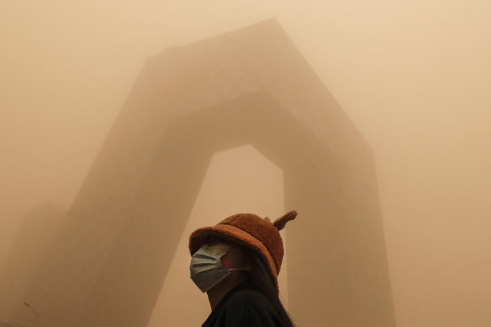 A woman wearing a face mask to help curb the spread of the coronavirus stands against the China Central Television (CCTV) building as capital city is hit by polluted air and a sandstorm in Beijing, Monday, March 15, 2021. The sandstorm brought a tinted haze to Beijing's skies and sent air quality indices soaring on Monday. (AP Photo/Andy Wong)
