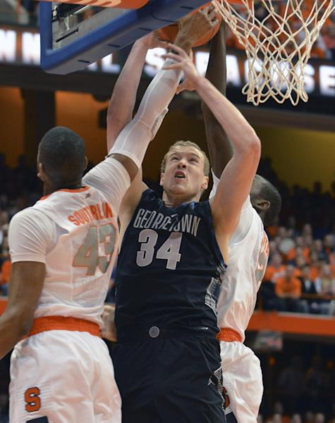 Georgetown's Nate Lubick, center, gets fouled by Syracuse's James Southerland, left, as Baye Mousa Keita defends during the first half of an NCAA college basketball game in Syracuse, N.Y., Saturday, Feb. 23, 2013. (AP Photo/Kevin Rivoli)
