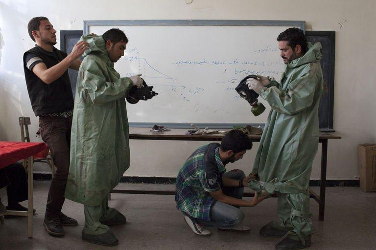 An Aleppo University student, shows Syrian citizens how to respond to a chemical attack on September 15, 2013