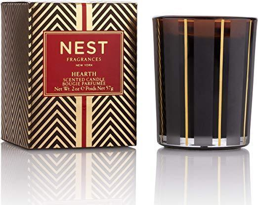 """<h3>Nest Fragrances Hearth Candle</h3><br>This festive votive said to contain """"the aroma of a wintertime fire"""" is infused with rich oud wood with frankincense and hints of smoky embers. <br><br><strong>NEST New York</strong> Classic Candle- Hearth, 8.1 oz, $, available at <a href=""""https://go.skimresources.com/?id=30283X879131&url=https%3A%2F%2Fwww.nestnewyork.com%2Fproducts%2Fhearth-classic-candle-1"""" rel=""""nofollow noopener"""" target=""""_blank"""" data-ylk=""""slk:NEST New York"""" class=""""link rapid-noclick-resp"""">NEST New York</a>"""
