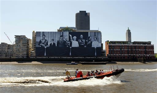 A boat passes a giant image hanging from a building on the south bank of the River Thames in London showing Britain's Queen Elizabeth II, fifth left, and from left the royal family, Prince Charles, Prince Edward, Prince Andrew, Earl Mountbatten, Prince Phillip, Mark Phillips and Princess Anne standing on the balcony of Buckingham Palace during the Queen's 1977 Silver Jubilee, Friday, May 25, 2012. The giant canvas, measuring 100 meters by 70 meters and weighing nearly two tons, was officially unveiled on Friday and will be displayed until the end of June, in celebration of the Diamond Jubilee, marking the Queen's 60 year reign. (AP Photo/Matt Dunham)