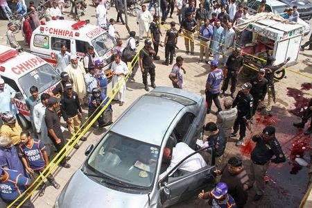 Police officers inspect a car after unidentified gunmen carried an attack on a prominent Pakistani cleric in Karachi