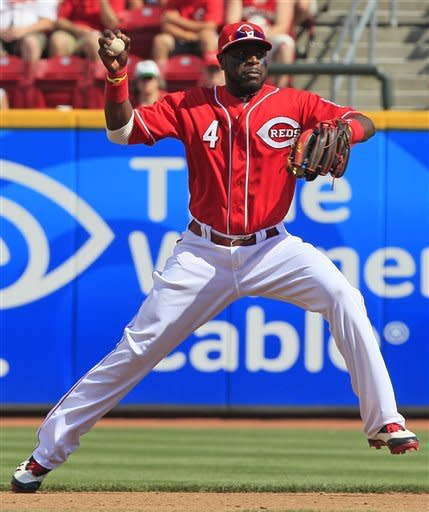 Cincinnati Reds second baseman Brandon Phillips (4) fields a ground ball hit by Minnesota Twins' Ben Revere with his bare hand in the fourth inning of a baseball game on Saturday, June 23, 2012, in Cincinnati. Phillips threw Revere out at first. (AP Photo/Al Behrman)