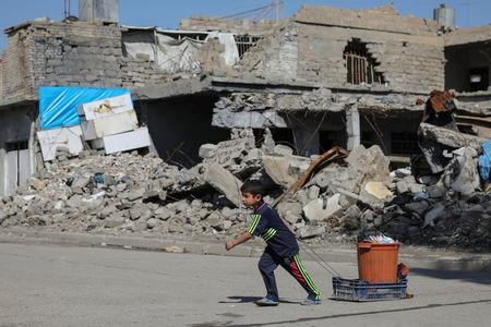 A boy pulls his belongings along a street in eastern Mosul