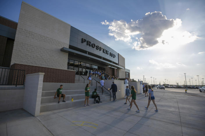 People walk to the entrance during the opening of the new Children's Health Stadium at Prosper ISD on Saturday, Aug. 17, 2019, in Prosper, Texas. Democrats are out to show they're serious about flipping Texas in 2020 by holding Thursday's presidential debate in Houston. Republicans are coming off their worst election in Texas in a generation. Fast-changing suburbs are trending more liberal, and Democrats are counting on more left-leaning voters moving in to turn the state blue. But that transformation may not arrive by 2020, and the GOP is closely watching conservative bastions like the booming Dallas suburbs. (AP Photo/Nathan Hunsinger)