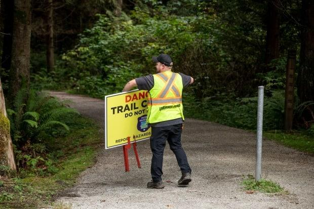 A Vancouver Parks worker removes a sign while reopening trails in Stanley Park in Vancouver on Monday. (Ben Nelms/CBC - image credit)