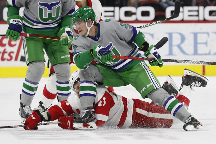 Carolina Hurricanes' Andrei Svechnikov (37) tangles with Detroit Red Wings' Dennis Cholowski (21) during the first period of an NHL hockey game in Raleigh, N.C., Saturday, April 10, 2021. (AP Photo/Karl B DeBlaker)