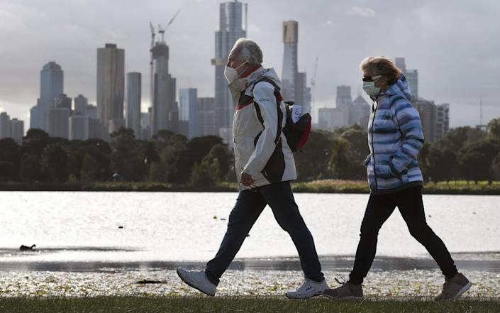 People walk along Albert Park lake in Melbourne on July 13, 2020, as five million people in Australia's second-biggest city began a new lockdown following a resurgence of coronavirus cases. - William West/AFP