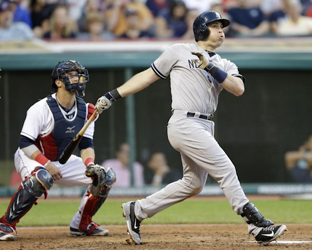 New York Yankees' Mark Teixeira watches his ball after hitting a two-run home run off Cleveland Indians starting pitcher Josh Tomlin in the fifth inning of a baseball game Wednesday, July 9, 2014, in Cleveland. Derek Jeter scored on the play. Cleveland Indians catcher Yan Gomes watches. (AP Photo/Tony Dejak)