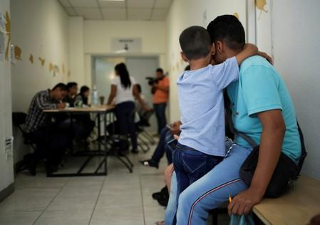 A man and his son from El Salvador wait for a turn to apply for U.S. asylum at the premises of the state migrant assistance office in Ciudad Juarez