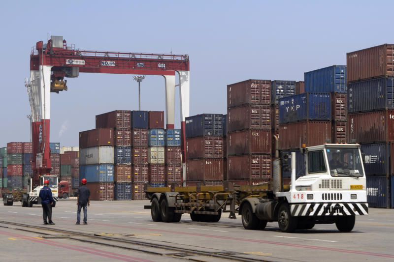 In this July 24, 2019, photo, workers watch as a truck passes by stacks of shipping containers at a port in Yingkou in northeastern China's Liaoning Province. Authorities in China's rust-belt region are looking for support for its revival from Beijing's multibillion-dollar initiative to build ports, railways and other projects abroad. (AP Photo/Olivia Zhang)