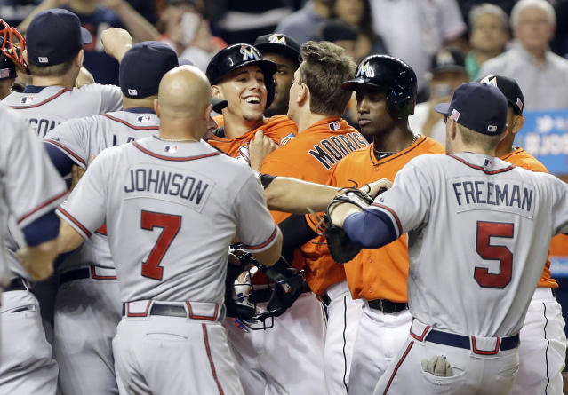Miami Marlins starting pitcher Jose Fernandez, center, is surrounded by Atlanta Braves players at home plate after an altercation broke out when Fernandez crossed home plate after hitting a solo home run in the sixth inning during a baseball game, Wednesday, Sept. 11, 2013, in Miami. (AP Photo/Lynne Sladky)