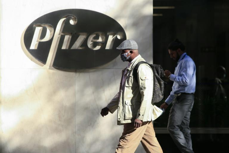 People walk by the Pfizer world headquarters in New York on November 9, 2020