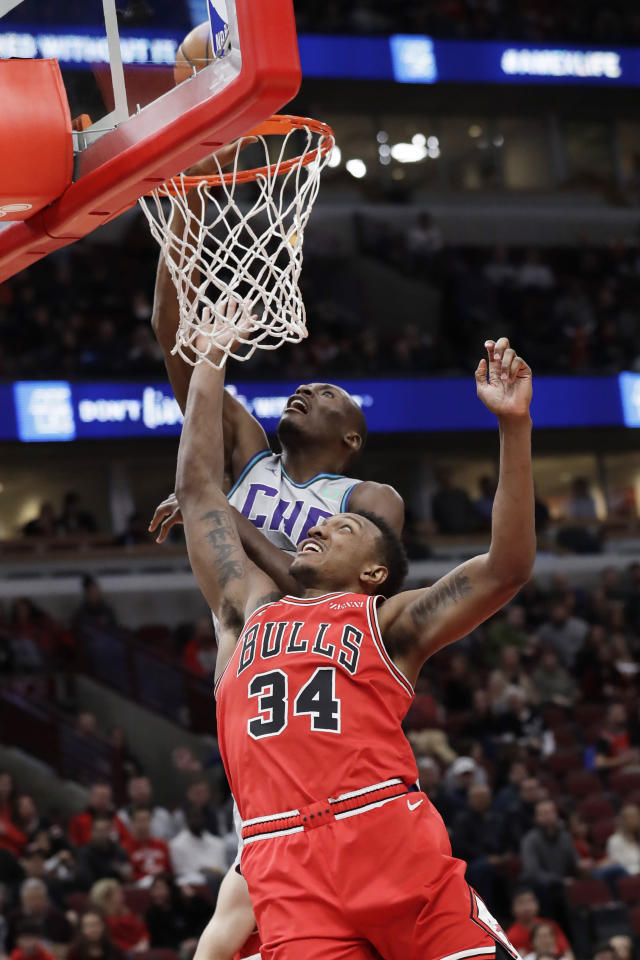 Charlotte Hornets center Bismack Biyombo, top, shoots against Chicago Bulls center Wendell Carter Jr., during the first half of an NBA basketball game Friday, Dec. 13, 2019, in Chicago. (AP Photo/Nam Y. Huh)