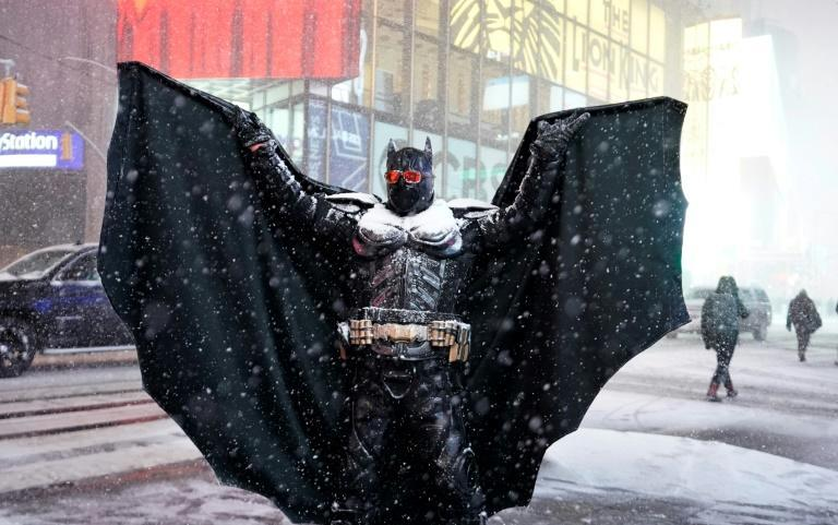 A person wearing a Batman costume stands under the snow in Times Square in New York City, December 16, 2020