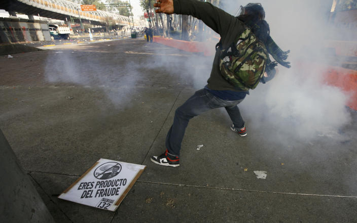 """A demonstrator throws a stone to police during protests against new Mexican President Enrique Pena Nieto's rule, outside the National Congress, in Mexico City, Saturday, Dec. 1, 2012. Pena Nieto took the oath of office as Mexico's new president on Saturday amid protests inside and outside the congressional chamber where he swore to protect the constitution and laws of the land. At least two protesters were injured, one gravely. The sign on the floor reads in Spanish """" you are a product of fraud """" referred to Pena Nieto.(AP Photo/Marco Ugarte)"""