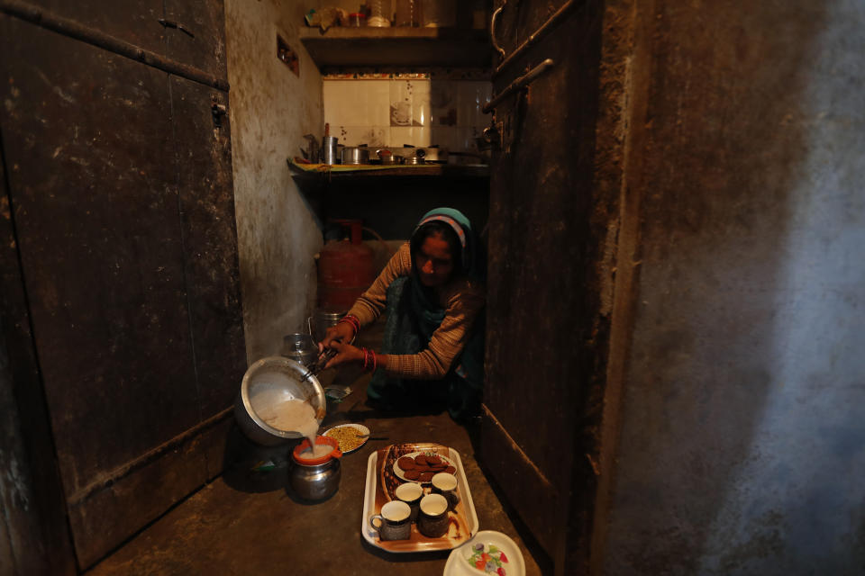 Indian farmer Ram Singh Patel's wife Kantee Devi prepares morning tea for her family members at their village house in Fatehpur district, 180 kilometers (112 miles) south of Lucknow, India, Saturday, Dec. 19, 2020. Patel's day starts at 6 in the morning, when he walks into his farmland tucked next to a railway line. For hours he toils on the farm, where he grows chili peppers, onions, garlic, tomatoes and papayas. Sometimes his wife, two sons and two daughters join him to lend a helping hand or have lunch with him. (AP Photo/Rajesh Kumar Singh)