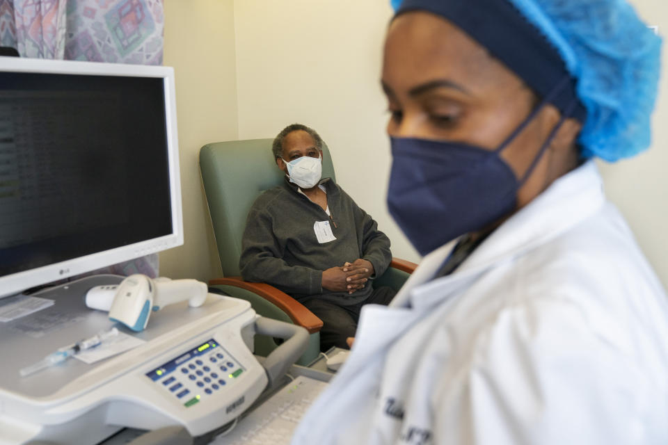 In this Wednesday, Feb. 10, 2021, photo the Rev. James Coleman, 70, waits as his COVID-19 vaccine is prepared by nurse practitioner Ifreke Udodong, at United Medical Center in southeast Washington. (AP Photo/Jacquelyn Martin)