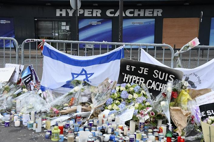 A picture taken on January 16, 2015 in Paris shows flowers, candles and an Israeli flag laid as a tribute to the victims of the attack which killed four people at the Jewish supermarket in Porte de Vincennes by jihadist gunman Amedy Coulibaly (AFP Photo/Bertrand Guay)