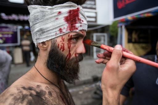 An Iraqi actor puts on make-up to play an injured anti-government protester ahead of a performance in Tahrir Square in Baghdad
