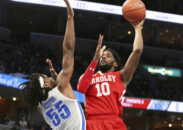 Memphis forward Precious Achiuwa (55) guards Bradley forward Elijah Childs (10) as he shoot to the basket in the first half of an NCAA college basketball game Tuesday, Dec. 3, 2019, in Memphis, Tenn. (AP Photo/Karen Pulfer Focht)