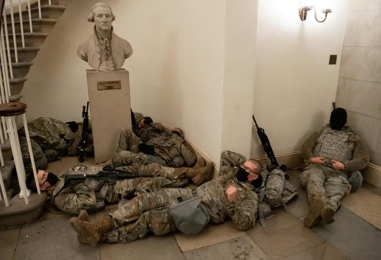 Members of the National Guard rest in the Rotunda of the US Capitol after security was beefed up following the attack on the building by supporters of President Donald Trump