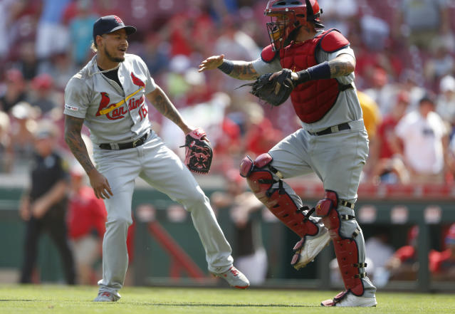 St. Louis Cardinals relief pitcher Carlos Martinez, left, and catcher Yadier Molina celebrate the team's 5-4 win over the Cincinnati Reds in a baseball game, Sunday, Aug. 18, 2019, in Cincinnati. (AP Photo/Gary Landers)