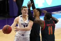 Northwestern forward Miller Kopp, left, looks to pass the ball as Maryland guard Hakim Hart, center, and guard Darryl Morsell defend during the second half of an NCAA college basketball game in Evanston, Ill., Wednesday, March 3, 2021. (AP Photo/Nam Y. Huh)