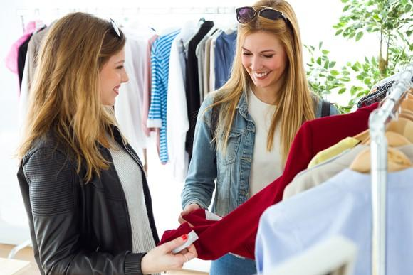 Two smiling women look at a red top on a rack of clothes.