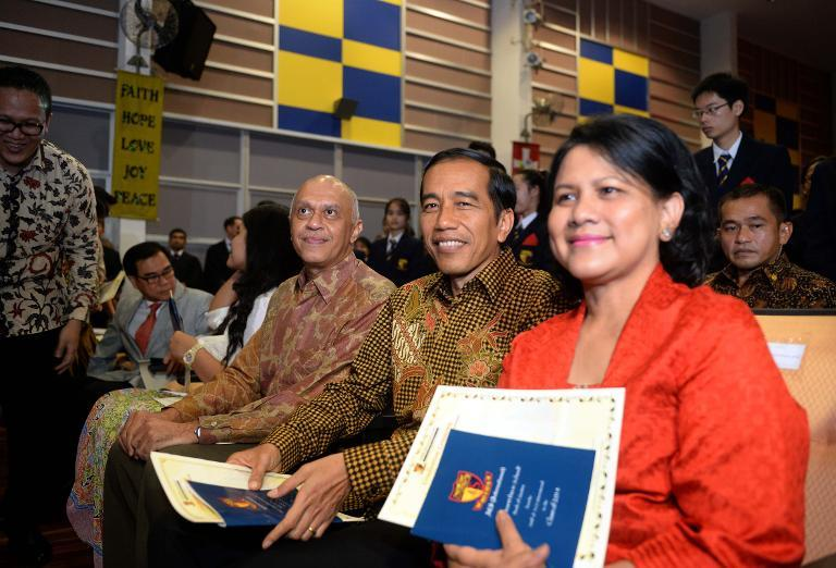 Indonesian President Joko Widodo (C) and First Lady Iriana attend the high school graduation ceremony of their youngest son Kaesang Pangarep, at the Anglo-Chinese International School in Singapore, on November 21, 2014