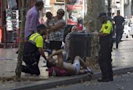 <p>Mossos d'Esquadra Police officers attend injured people after a van crashed into pedestrians in Las Ramblas, downtown Barcelona, Spain, August 17, 2017. (David Armengou/EPA/REX/Shutterstock) </p>