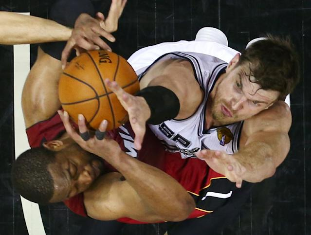 Miami Heat guard Dwyane Wade, left, and San Antonio Spurs center Tiago Splitter go after the rebound during in Game 1 of the NBA basketball finals on Thursday, June 5, 2014 in San Antonio. (AP Photo/Andy Lyons, Pool)