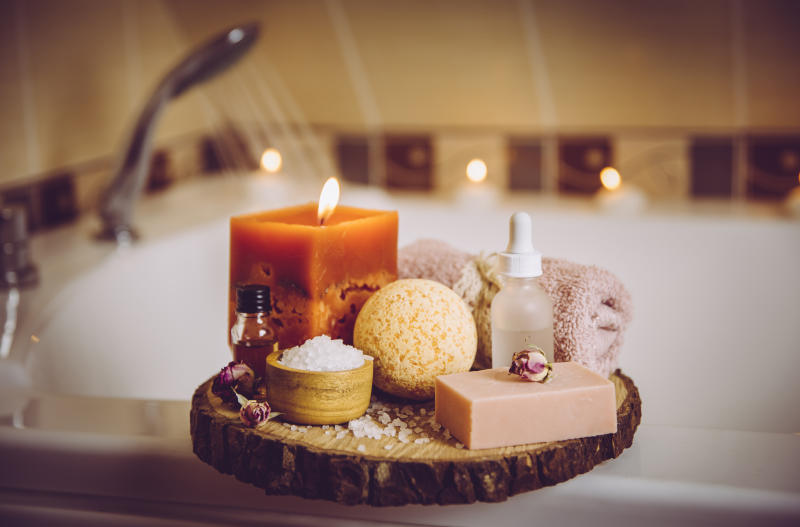 Home spa products on wooden tray: bar of soap, bath bomb, aroma bath salt, essential and massage oils, candle burning, rolled towel inside bathroom by tub running water. Modern Instagram style filter.