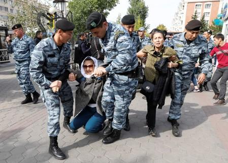 Kazakh law enforcement officers detain women during a rally held by opposition supporters in Nur-Sultan