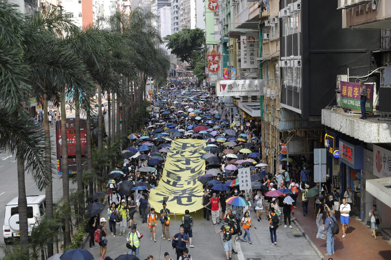 """Masked protesters walk next to a banner with the words """"May Glory be to Hong Kong"""" in Hong Kong on Saturday, Oct. 5, 2019. All subway and trains services are closed in Hong Kong after another night of rampaging violence that a new ban on face masks failed to quell. (AP Photo/Vincent Thian)"""