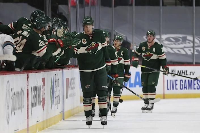 Minnesota Wild's Nick Bjugstad (27) high fives teammates on the bench after scoring a goal against the San Jose Sharks in the second period of an NHL hockey game Sunday, Jan. 24, 2021, in St. Paul, Minn. (AP Photo/Stacy Bengs)