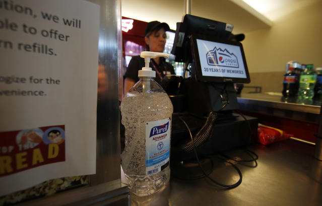 A large bottle of hand sanitizer stands next to the cash register at a food stand in Pepsi Center before the Colorado Avalanche host the New York Rangers in the first period of an NHL hockey game Wednesday, March 11, 2020, in Denver. (AP Photo/David Zalubowski)