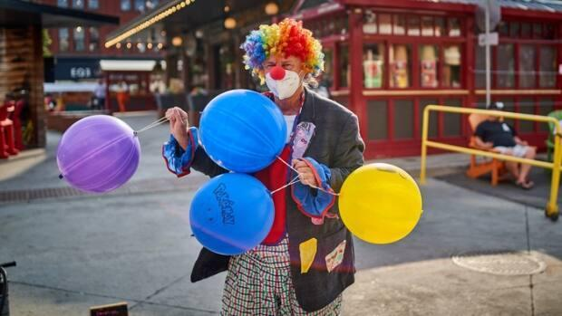 A busker in a clown wig and a COVID-19 mask performs in Ottawa's ByWard Market on July 5, 2021.          (David Richard/Radio-Canada - image credit)
