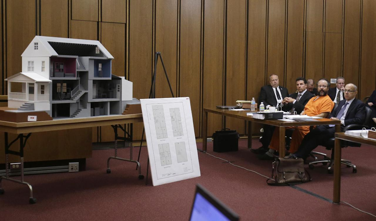 Ariel Castro sits close to a model of the house on Seymour Ave. , where three women were held in the courtroom during the sentencing phase Thursday, Aug. 1, 2013, in Cleveland. Three months after an Ohio woman kicked out part of a door to end nearly a decade of captivity, Castro, a onetime school bus driver faces sentencing for kidnapping three women and subjecting them to years of sexual and physical abuse. (AP Photo/Tony Dejak)
