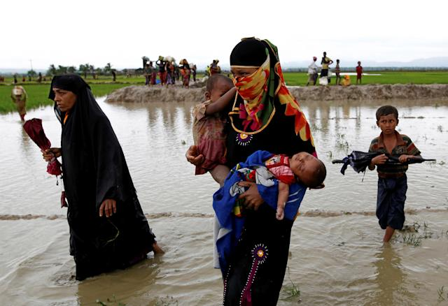 <p>A Rohingya refugee woman carry children while walking in the water after travelling over the Bangladesh-Myanmar border in Teknaf, Bangladesh, Sept. 1, 2017. (Photo: Mohammad Ponir Hossain/Reuters) </p>