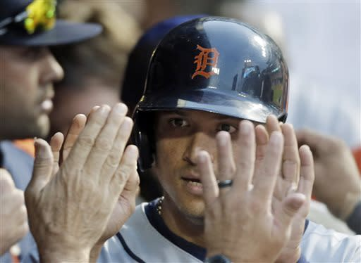 Detroit Tigers' Victor Martinez is greeted in the dugout after scoring on a double by Jhonny Peralta in the fifth inning of a baseball game Friday, July 5, 2013, in Cleveland. (AP Photo/Mark Duncan)