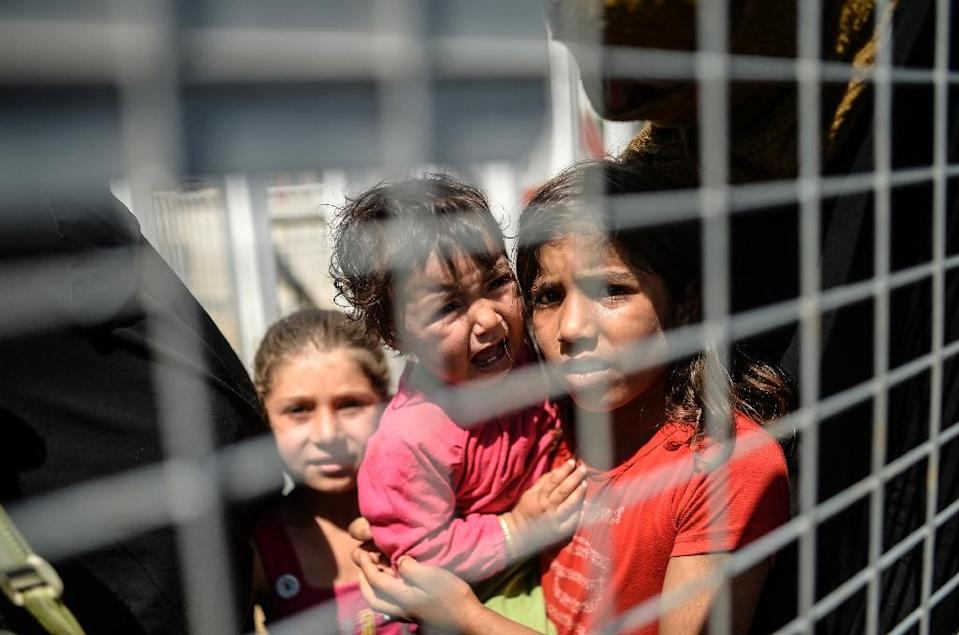 Syrian refugees wait behind a fence prior to go back to the northern Syrian town of Tal Abyad at the Turkish border post of Akcakale, the province of Sanliurfa, on June 17, 2015 (AFP Photo/Bulent Kilic)