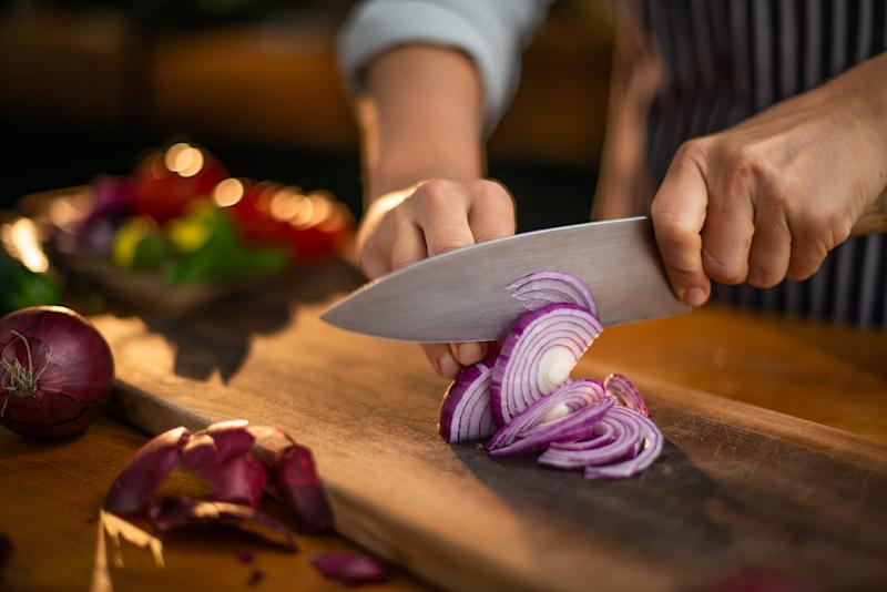 A cook cuts red onions on a wooden cutting board. (Getty)