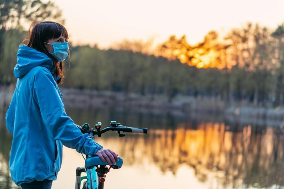 Virus. A woman with a bicycle and a protective medical mask is standing in the park.
