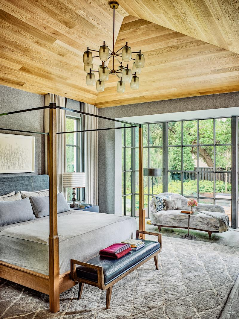 The master bedroom is furnished with a Holly Hunt bed and a bench and lighting by Arteriors.