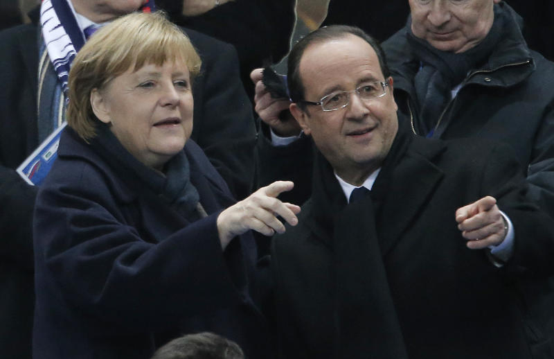 French President Francois Hollande, right, and German Chancellor Angela Merkel chat before the soccer friendly match between France and Germany in the Stade de France in Saint-Denis, France, Wednesday, Feb.6,2013. (AP Photo/Francois Mori)