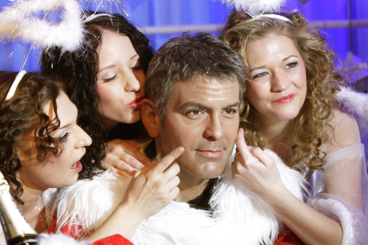 Women wearing Christmas angels costumes pose with a  wax figure of U.S. actor George Clooney which is dressed in a Santa Claus outfit, at the German 'Madame Tussauds' in Berlin December 5, 2008. REUTERS/Hannibal Hanschke (GERMANY)