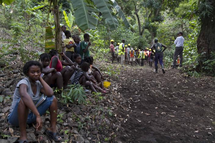 In this April 10, 2012 photo, people watch as workers build a road through the mountains that will lead to an exploratory drill site in the department of Trou Du Nord, Haiti. Haiti's land may yet hold the solution to centuries of poverty: there is gold hidden in its hills, and silver and copper too. Now, two mining companies are drilling around the clock to determine how to get those metals out, and how much it might cost. (AP Photo/Dieu Nalio Chery)